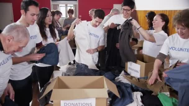 Charity volunteers in white printed t. shirts sorting through donated clothing