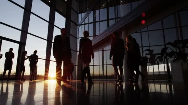 Business people walking through building at sunset