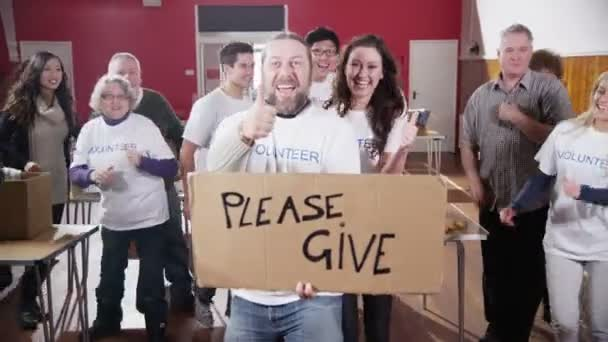Group of charity volunteers give thumbs up to camera with a Please Give sign