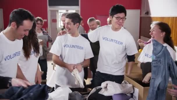 Charity volunteers in printed  t shirts sort through donated food and clothing
