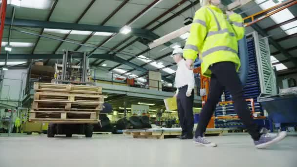 Busy warehouse workers lifting and moving goods and materials