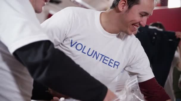 Charity volunteers in printed t  shirts are sorting through donated goods