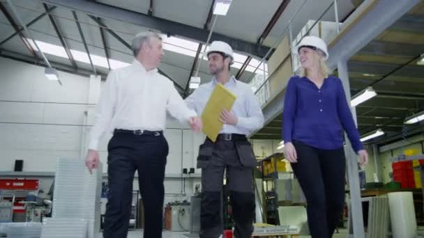 Happy team of engineers or industrial workers walk and chat together