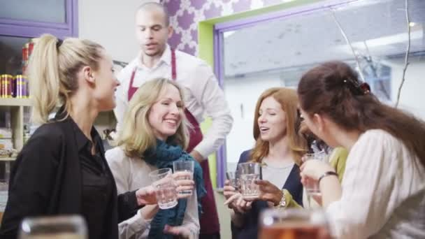 Happy group of female friends in a cafe raise their glasses for a toast