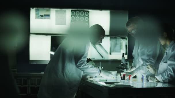sötét laboratóriumban dolgozó tudósok
