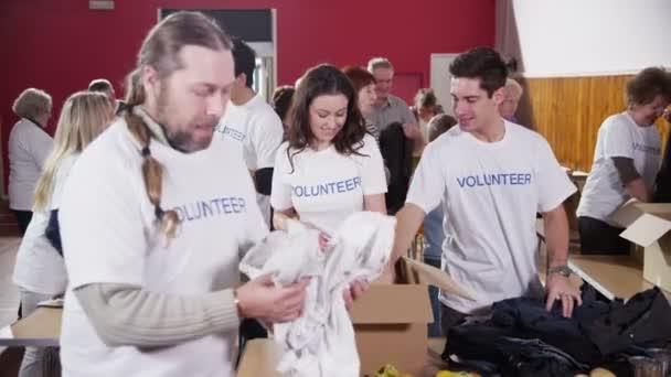 Dobrovolníci charity třídění prostřednictvím darované zboží