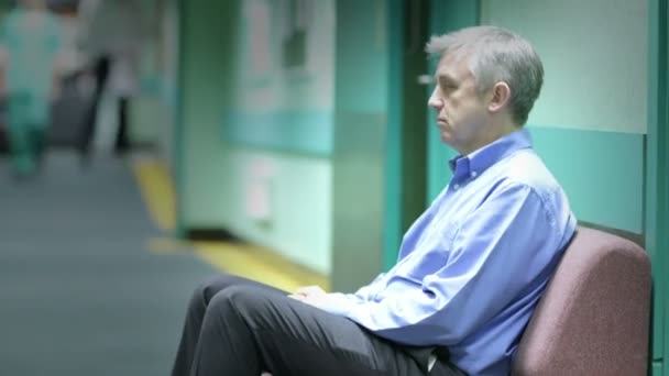 Worried man sits in hospital waiting area