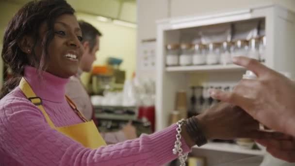 přátelské ženské baristů v kavárně slouží zákazníkům