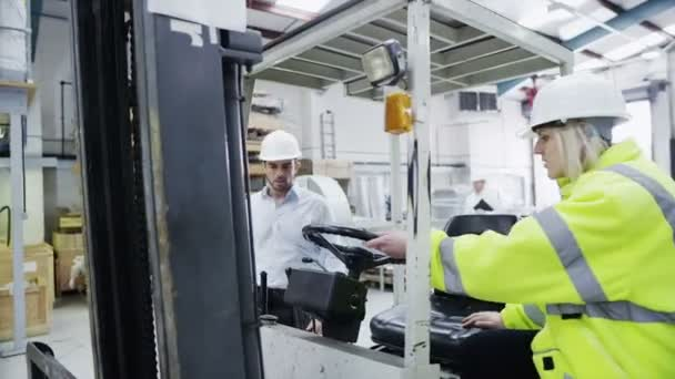 ženské vysokozdvižný vozík řidič začíná její posun v továrně nebo skladu