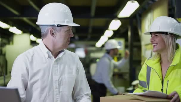 Workers in a warehouse with a laptop computer are preparing goods for delivery