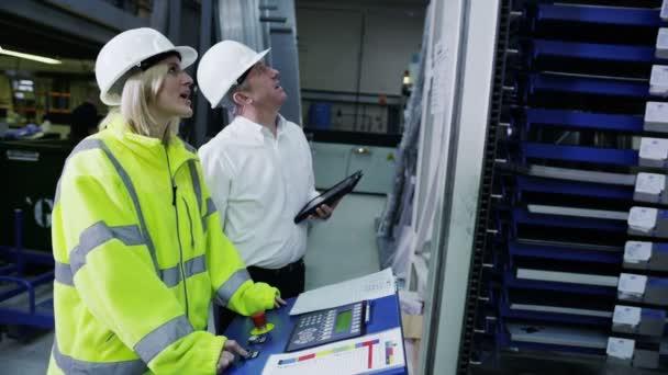 starší tovární správce ukazuje jeho zaměstnanci obsluhovat stroje