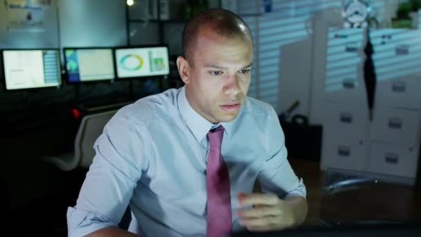Businessman working late looks tired and uncomfortable as he loosens his tie