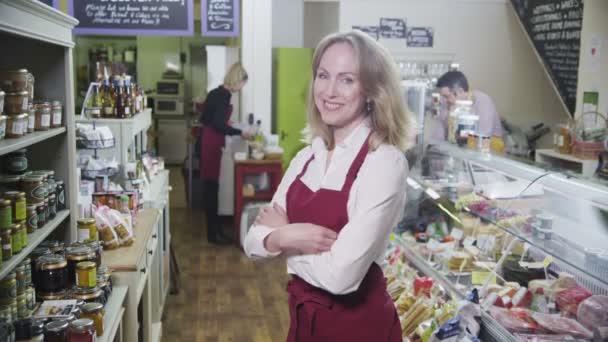 portrét šťastné ženské obchodník v lahůdkářství nebo potraviny uchovávat