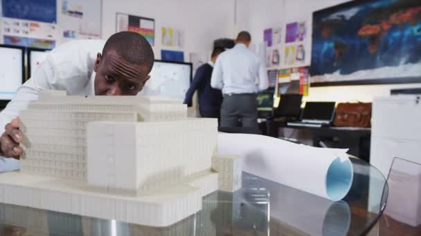 Male architect or engineer looking at concept models of new development