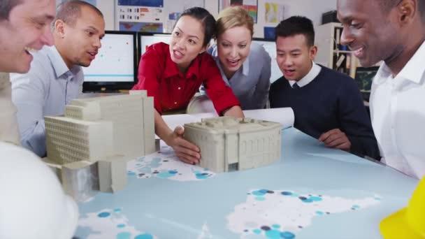 šťastný a atraktivní smíšený etnické tým architektů a inženýrů v jednání