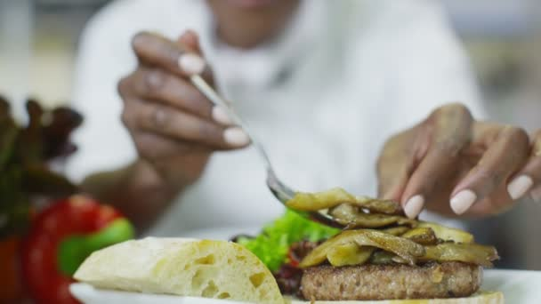 Delicious gourmet burger is being given the finishing touches by the chef