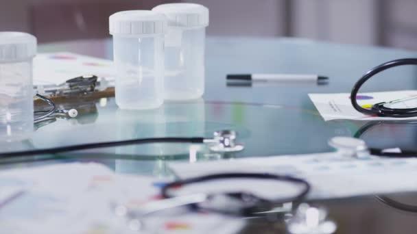 tištěné diagramy a vyřazené Stetoskopy na skleněný stůl v lékařském zařízení
