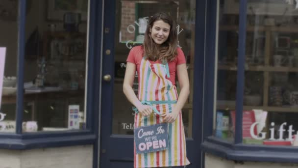 Shopkeeper stands outside of shop