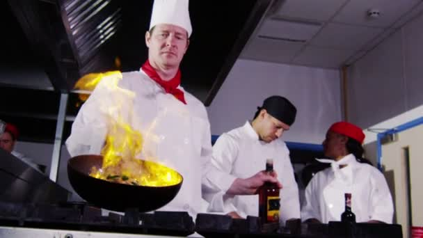 Professional chef in a commercial kitchen cooking flambe style.