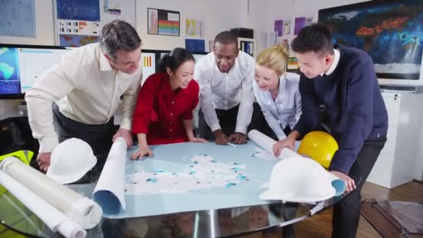 Cheerful mixed ethnicity team of architects or engineers looking at world map
