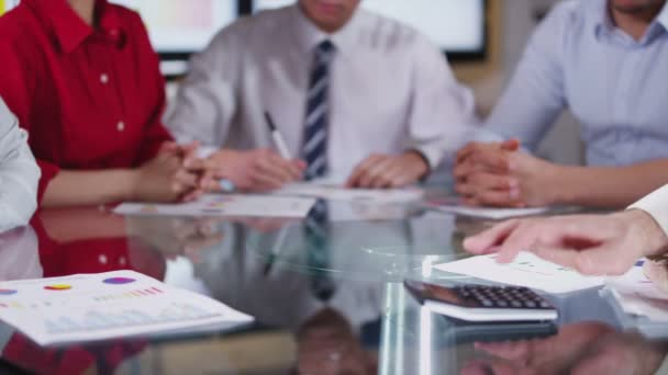Business team in meeting, hands reach across the table to shake hands on a deal