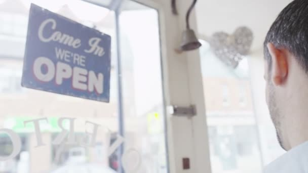 Shopkeeper turns Closed sign to Open