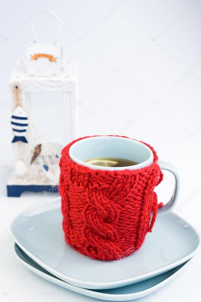 taza azul con tapa roja tejida y casa farol decorativo — Foto de ...