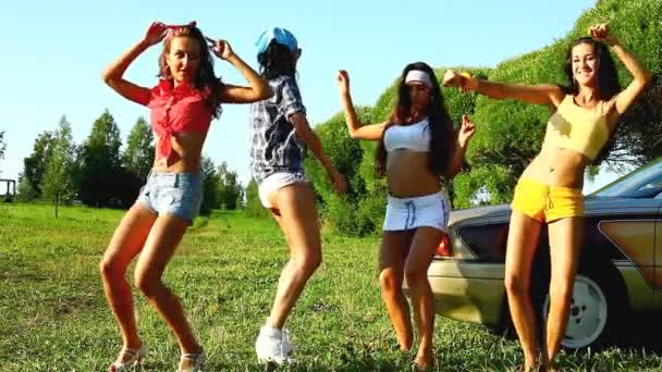 girls dance near car at summer sunset