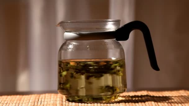 green tea brew in glass teapot