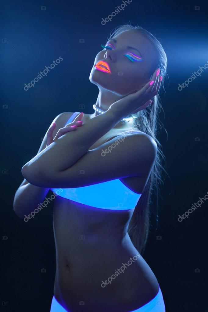 Sexy girl with neon make-up dance in ultraviolet