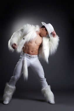 Athletic striptease dancer in white cowboy costume