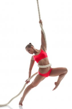 Graceful woman hanging on rope in studio