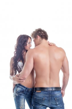 Embrace of semi-nude couples posing in jeans
