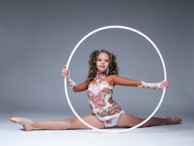 Adorable young artistic gymnast sitting on split