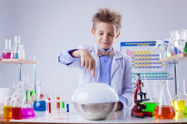 Smiling boy conducting experiment in chemistry lab