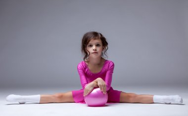 Adorable little gymnast posing on split in studio