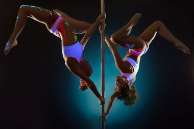 Sporty girls dancing on pole under UV light