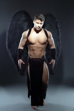 Handsome muscular guy posing as fallen angel