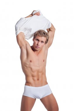 Image of sexy young man takes off his t-shirt