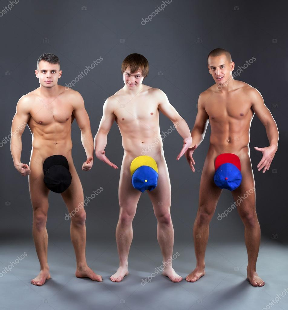 Cheerful Naked Guys Posing In Colorful Caps Stock Photo