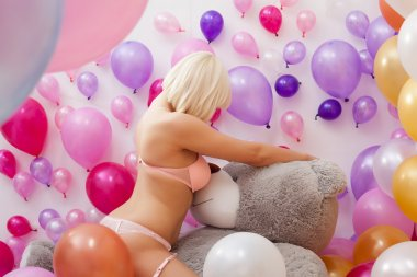 Curvy young blonde posing hugging teddy bear