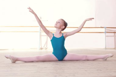 Flexible little ballerina posing sitting on split