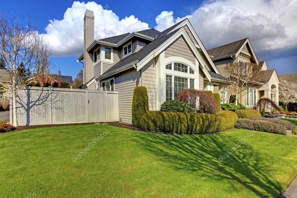 Classica casa americana con recinzione ed erba verde for Piani casa americana