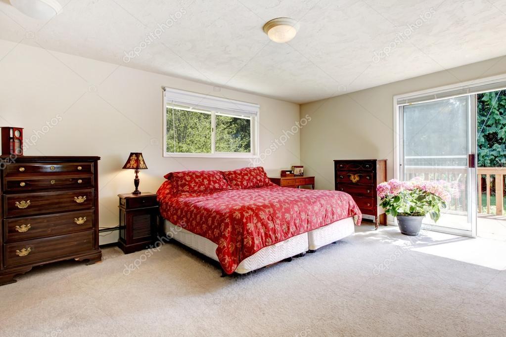 Bedroom with red bed, open balcony door and beige walls ...