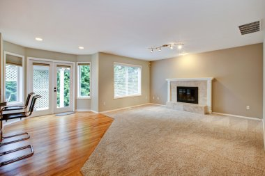 Large bright empty new living room with fireplace.