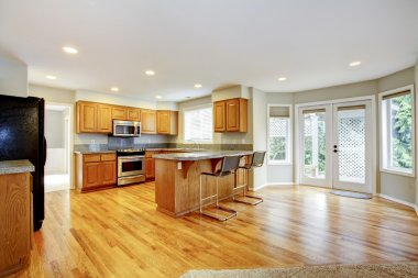 Large empty open kitchen with living room with balcony doors.