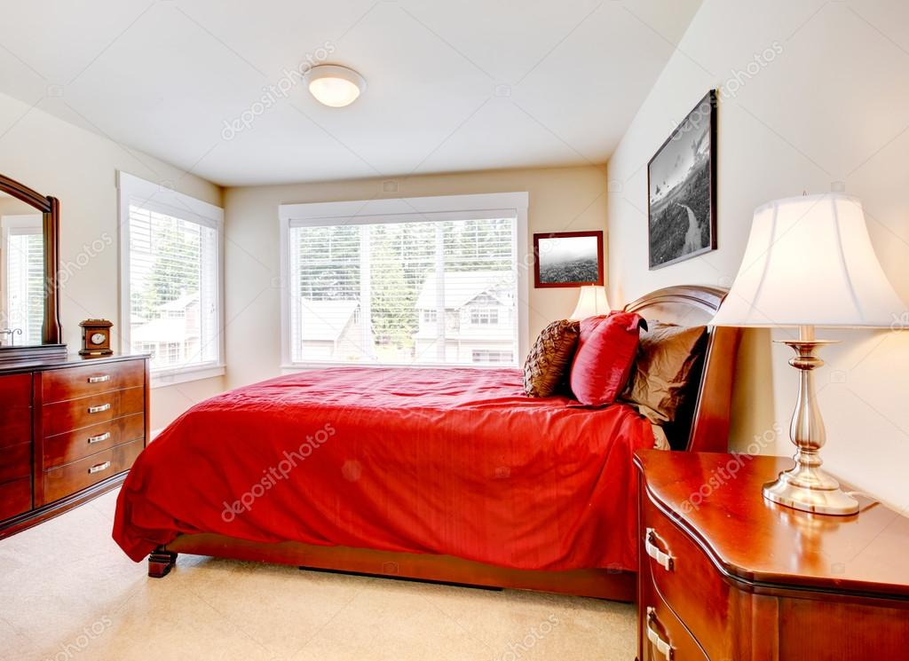 dormitorio con cama roja con muebles de madera y dos ventanas — Foto ...