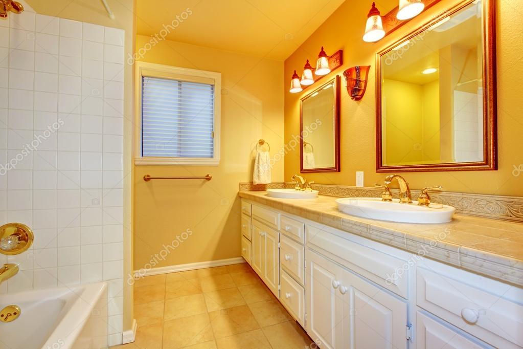 Pareti Bianche E Oro : Bagno con armadi bianchi e pareti gialli oro u foto stock