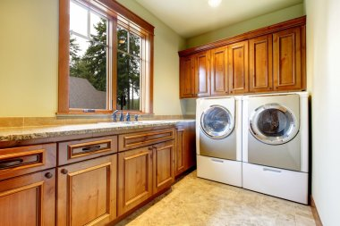 Luxury laundry room with wood cabinets.