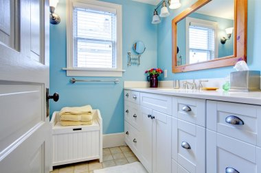 Blue and white bathroom with lots of storage space.